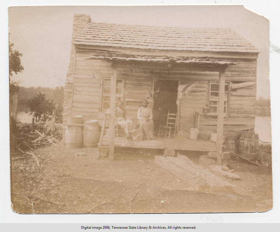 Two African-American women and baby on porch of river dwelling