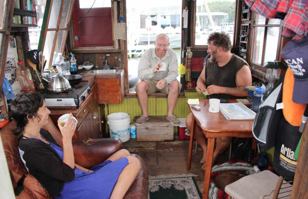 Wes Modes (far right) and his shipmates Adrian Nankivell (middle), of New Zealand, and Penske Pocketknife (far left), of Santa Cruz, California, enjoy a cup of coffee in the shantyboat at Kenlake Marina early Tuesday morning. Pocketknife is a fellow artist who has been a friend of Modes' for approximately seven years and had joined the trip two days previous to this photo. Nankivell is a friend of Modes' for 15 years after meeting at the Burning Man festival in the United Kingdom and accompanied Modes for several weeks on the trip down the Tennessee River. Photo by Rachel Keller/The Tribune-Courier